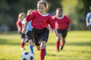 Girl Kicks Ball Up Field